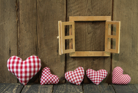 Wooden window frame and handmade red, white checked hearts of frabric on wooden background in country style  photo