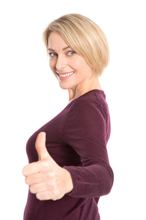 thumbs up woman: Happy best age model with thumb up - isolated over white.