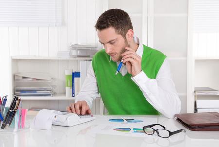 bookkeeper: Contador joven que trabaja en el escritorio.