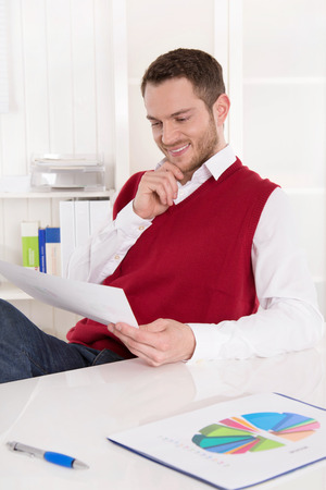outgoings: Smiling businessman with diagrams at desk.