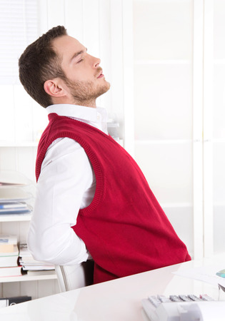 Pain Management: Young attractive businessman with rheumatism at office.