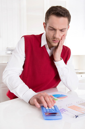 outgoings: Pensive controller working with diagrams at desk. Stock Photo