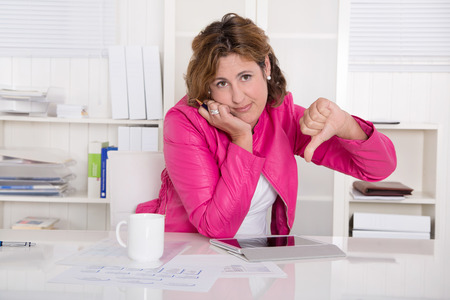 outgoings: Frustrated secretary with thumb down at desk at office