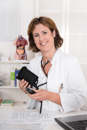 Attractive brunette physician in uniform with blood pressure device at desk  photo