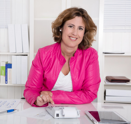 Successful secretary sitting smiling at desk at office