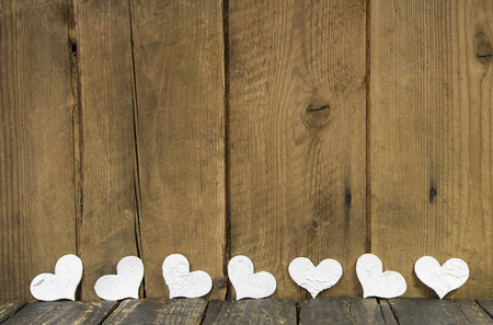 Wooden old rustic background in shabby style with six wihte hearts. photo