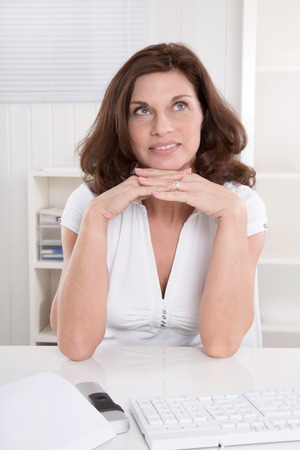 consider: Thoughtful bruentte senior businesswoman at desk at office.