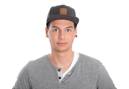 Isolated potrait of young serious male teenager with cap on white background.  Imagens