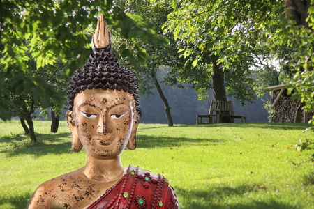 Buddha sculpture in a green japanese garden - concept for meditation. photo