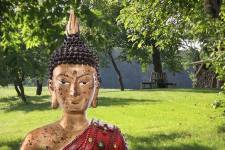 thai believe: Buddha sculpture in a green japanese garden - concept for meditation. Stock Photo