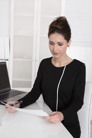 financial controller: Young business woman sitting at desk reading paper. Stock Photo