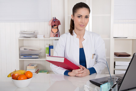 informing: Young doctor informing about healthy food sitting at desk. Stock Photo