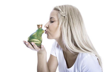 Concept for love, partnership - young teenager is kissing a frog in her hand isolated over white Imagens - 27883935