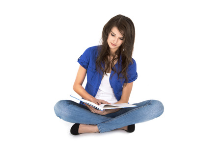 long legged: Attractive female student is learning with a book sitting with crossed legs on the ground isolated over white background