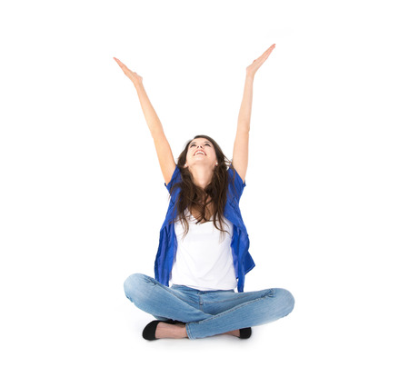 publicity: Female trainee sitting with crossed legs on the ground wiht hands up isolated over white background   Stock Photo