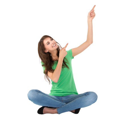 Adorable female student sitting with crossed legs is pointing with fingers   photo