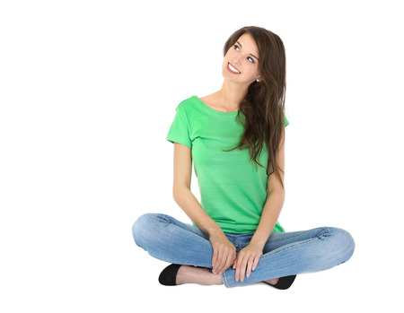 sideways glance: Adorable female trainee in casual clothes sitting with crossed legs on the floor  Stock Photo
