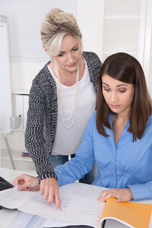 Senior businesswoman controlling a young sitting at desk.