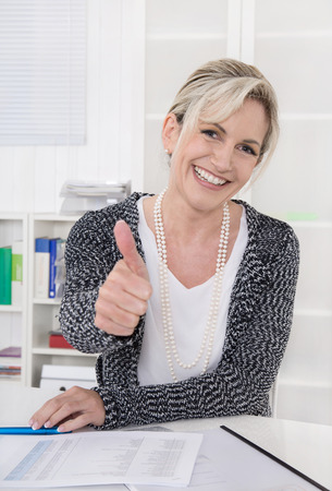 Smiling older business woman sitting at desk with thumbs up.
