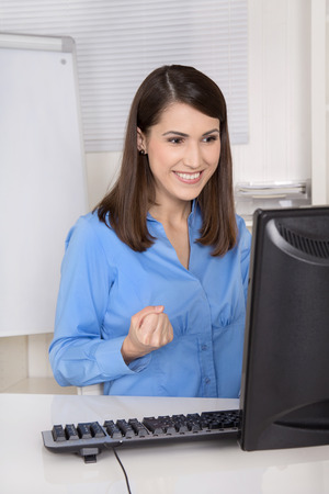 Successful young happy business woman sitting in her office. Stock Photo