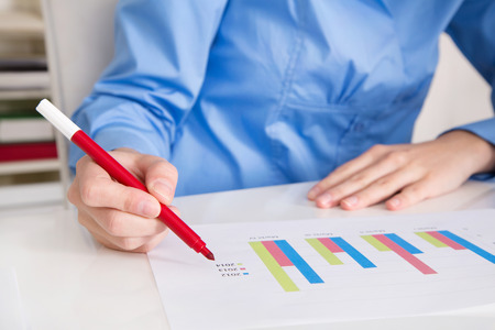 outgoings: Woman holding a red pencil analyzings business papers. Stock Photo