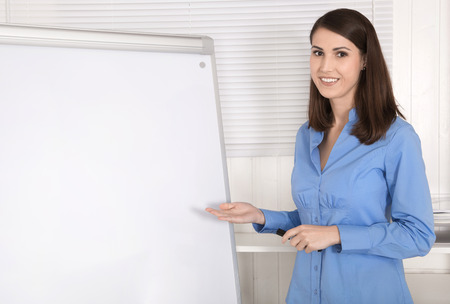 flip chart: Attractive beautiful business woman standing before a flip chart.