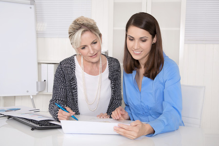 financial controller: Two attractive business woman in meeting analyzing budget. Stock Photo