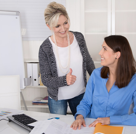 woman boss: Senior female manager praise her young assistantt in the office.
