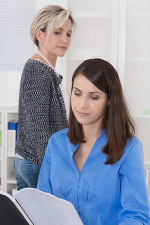 annoying: Bullying at workplace: older business woman is jealous.