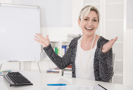 Satisfied and cheering senior business woman sitting at desk.