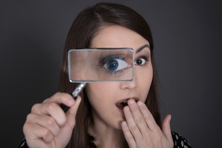 Curious and shocked business woman in black holding magnifying glass. photo