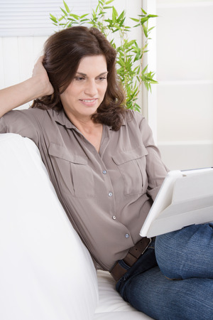 Pretty satisfied and smiling older woman at home - talking with tablet pc. photo