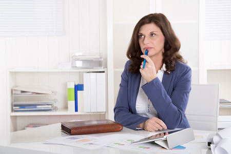 doubt: Portrait: Unhappy older pensive business woman sitting at desk. Stock Photo