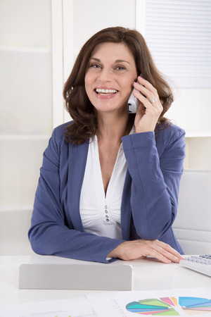 Portrait of a female beautiful senior manager calling at desk. photo