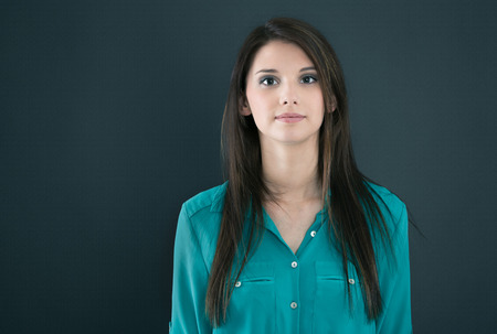 emotionless: Portrait of a isolated young woman on a black board looking emotionless.
