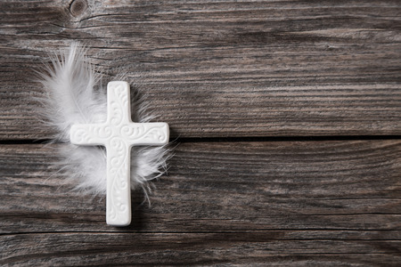 Mourning: White cross with feather on an old rustic
