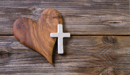 sacrificio: corazón de oliva y cruz blanca para un obituario.
