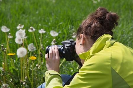 Junge Frau in der Freizeit macht Naturfotos im Gras.