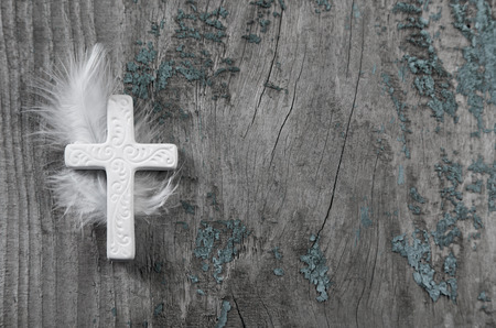obituary: Mourning: White cross with feather on an old rustic