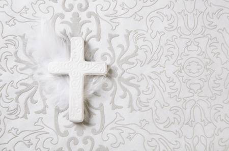 obituary: Mourning: white ceramic cross with feather for a obituary notice.