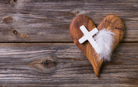 obituary: Wooden background - olive heart and white cross for an obituary notice.