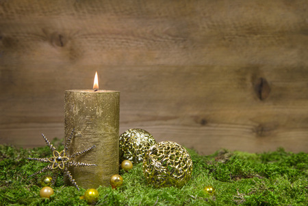moos: First advent: golden candle burning before a wooden background.