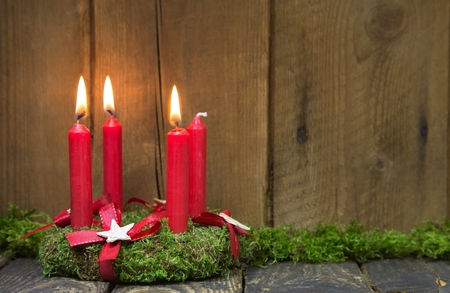 Advent or christmas wreath with four red wax candles on wooden background. photo