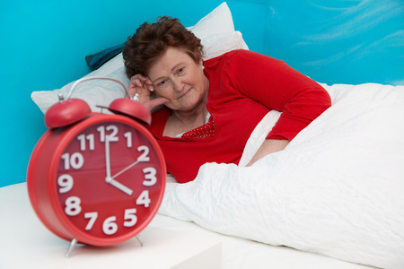 Senior woman in bed ill and suffered of sleeplessness. photo