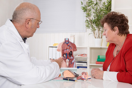 professional practice: Senior doctor with an older woman explaining the human body.