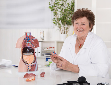 Portrait of happy older senior doctor explaining the human body with plastic torso. Stock Photo - 28446307