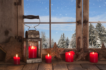 Country christmas decoration  wooden window decorated with red candles and latern View to the mountains  Stock Photo