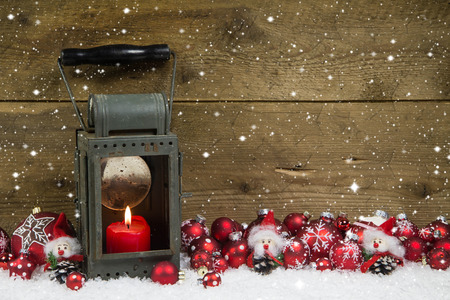 imp: Christmas latern with red candle and balls on wooden background  Idea for a greeting card