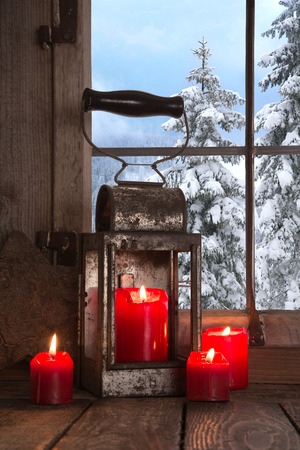 Old wooden windowsill decorated with four red christmas candles  View out to the snowbound trees in the mountains  photo