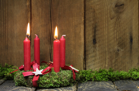 Advent or christmas wreath with four red wax candles on wooden background